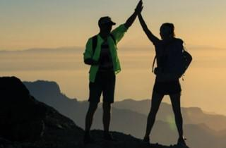 Two people high five on mountain top