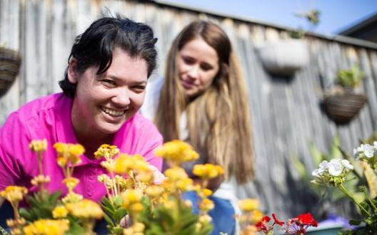 client and support worker in the garden